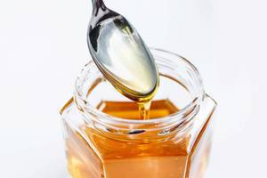 Close Up Photo of Honey running down Spoon into Honey Glass on white Background