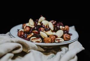 Close Up Photo of Nut Mix with Walnut, Almonds and Raisins on ceramic Plate