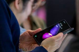 Close Up Photo of Person using the Samsung Galaxy Fold Smartphone with 5G and Foldable Display at a Fair