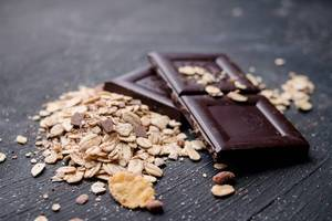 Close Up Photo of Pieces of Dark Chocolate next to Oatmeal on Black Wooden Table