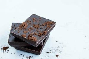 Close Up Photo of Pieces of Dark Chocolate stacked on each other with Cocoa Powder on white Background