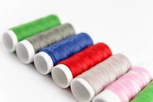 Close Up Photo of Sewing Thread in different colors laying next to each other on white Background