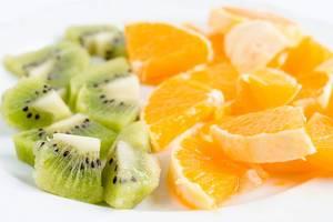Close Up Photo of Sliced Kiwi and Orange on White Background