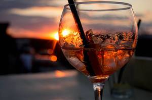 Close Up Photo of Spritz Veneziano Cocktail with Plastic Straw and Slice of Lime with Sunset in the Background