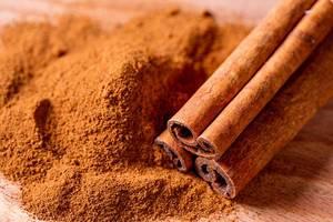 Close Up Photo of Three Cinnamon Rolls next to Cinnamon Powder on Wooden Table