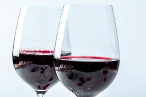 Close Up Photo of Two Wine Glasses half filled with Red Wine on White Background