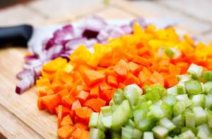Close Up Photo of Vegetables Celery, Carrot, Onion and Bell Pepper cut in Cubes on Wooden Cutting Board