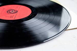 Close Up Photo of Vinyl Record on White Wooden Table