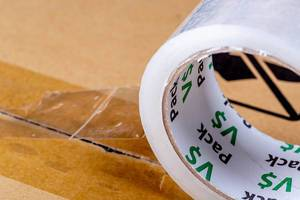 Close-up roll of adhesive tape on cardboard box. The concept of packing or sending