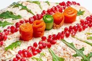 Close-up salad decorated with pomegranate seeds, arugula, carrot and cucumber