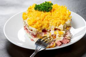 Close-up salad with boiled potatoes, eggs, ham and sauce on a white plate with a fork (Flip 2019)