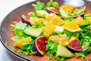 Close-up salad with lettuce, oranges, figs and mango on a plate (Flip 2019)