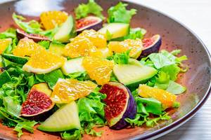 Close-up salad with lettuce, oranges, figs and mango on a plate