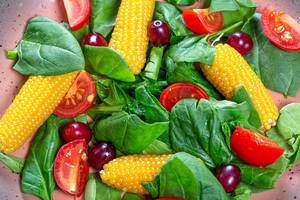 Close-up salad with spinach, tomatoes, corn and dogwood