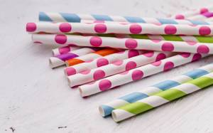 Close Up Shot of Colorful striped and dotted Paper Straws laying on Wooden Table