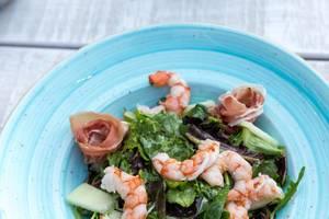 Close-up shot of shrimp salad with melon, prosciutto and lemon-caviar cream