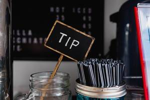 Close up shot of tip sign near coffee stirrers