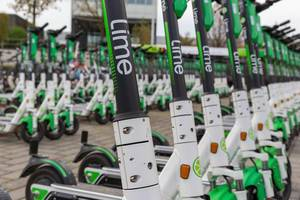 Close-up shot of various rows of Lime e-scooters parked in Cologne