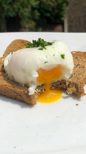 Close-up shows bitten off poached egg on a slice of wholemeal bread with liquid egg yolk, on a white table