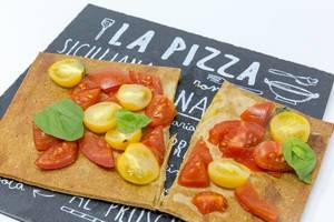 Close Up - The low carb vegan pizza crust made from chia an flaxseeds as a bruschetta topped with fresh cherry tomatoes and basil leaves