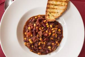 Close Up Top View Food Photo of Chili Con Carne with Ground Pork, Tomatoes, Beans and Corn with Slice of Bread