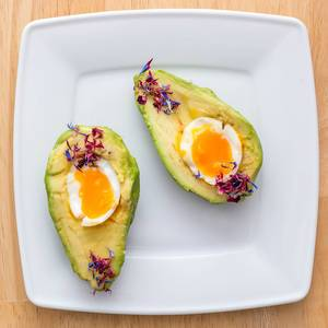 Close Up Top View Food Photo of Halved Avocado with Soft Boiled Egg on a White Plate