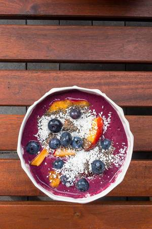 Close Up Top View Food Photo of Healthy Acai Bowl with Blueberry, Coconut Rasp and Peach