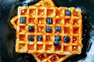 Close Up Top View Food Photo of Honey Glazed Belgian Waffles topped with Blueberries