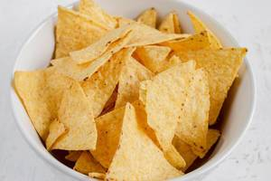 Close Up Top View Food Photo of Seasoned Tortilla Chips in a White Bowl on White Background
