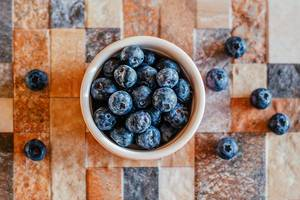 Close Up Top View Photo of Blueberries in Ceramic Bowl on Colorful Tiled Background