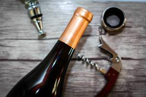 Close Up Top View Photo of Closed Wine Bottle with Corkscrew on Wooden Background