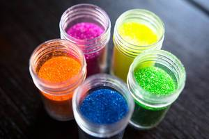 Close Up Top View Photo of Colorful Open Glitter Bottle Container