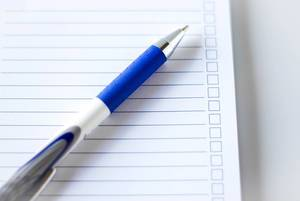 Close Up Top View Photo of Pen on To Do List Notebook on White Table