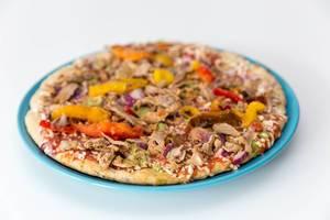 Close up Vegetarische Protein Pizza mit Leinsamen, Quinoa und pulled Soybeans von Garden Gourmet ausgepackt gefroren auf einem Teller