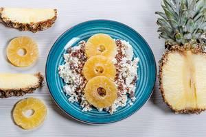 Close-up von Hüttenkäse mit Leinsamen und getrockneten Ananas Scheiben vor weißem Holzhintergrund mit frischen Ananas Stücken