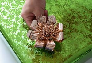 Closeup image of girls hands putting bow to  gift