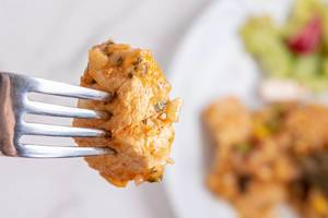 Closeup of Chicken Meat on the fork with blurred background