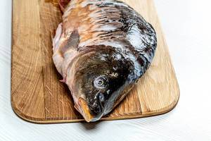 Closeup of fresh raw carp on kitchen Board