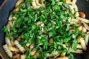 Closeup of pasta with spinach and mushrooms in a frying pan