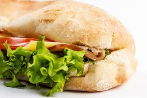 Closeup on Sandwich with Lettuce Cheese Ham and Tomato on white background