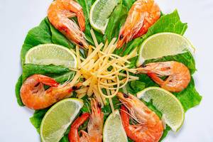 Closeup salad with romaine lettuce, shrimps, lime slices and grated cheese