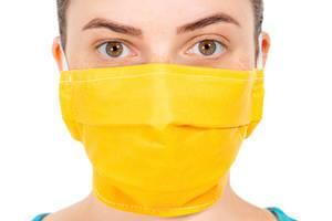 Closeup young girl face in yellow medical mask