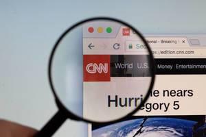 CNN-Logo am PC-Monitor, durch eine Lupe fotografiert