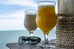 Cocktails and Sunglasses on a Table with Seaview in the Background  Flip 2019