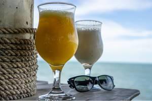Cocktails mit Fruchtsaft mit Sonnenbrille auf Holztisch vor Meerblick im Hintergrund