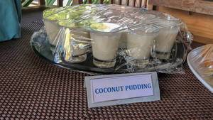Coconut pudding in glasses on black plate covered with plastic wrap at Constance Ophelia Resort in the Seychelles