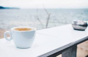 Coffee break at a beach bar. Sea background.