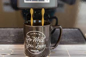 "Coffee break at rental office WeWork in Cologne: close-up of a coffee machine pouring a hot drink into a black cup with text ""Always do what you love"""