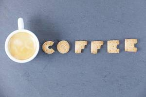 Coffee letters of biscuit and coffee cup, dark background