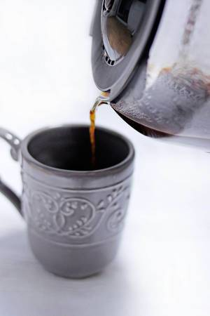 Coffee pot pouring hot beverage into a cup
